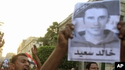 Protesters chant slogans and hold pictures of Khaled Said, as they rally in memory of him outside the Interior Ministry in Cairo, Jun 6, 2011
