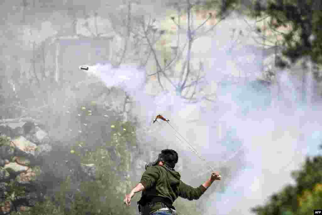 A Palestinian protester wearing a gas mask uses a slingshot to hurl back an Israeli-fired tear gas cannister during clashes in the village of Beit Sira, west of Ramallah, in the Israeli-occupied West Bank, following a demonstration demanding the return of the bodies of those killed by Israeli forces.