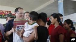 菲律賓總統阿基諾(左)星期二前往受到颱風襲擊的地區﹐探訪災民。