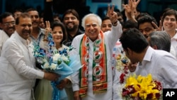 Congress party leader Kapil Sibal, center and his wife Promila Sibal flash victory signs as supporters present them with flower bouquets after Sibal filed his nomination papers for the upcoming parliamentary elections in New Delhi, India, March 20, 2014.