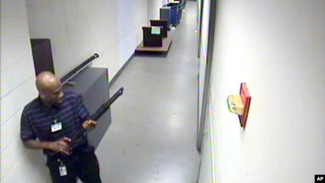 Image provided by FBI shows Aaron Alexis carrying a Remington 870 shotgun through hallways of building #197 at Washington Navy Yard, Sept. 16, 2013.