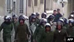 An image grab taken from AFP TV shows Syrian security forces walking towards anti-regime protesters as they attempt to reach the main square in the flashpoint city of Homs on January 1, 2012.