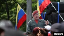 Un recorte de cartón de tamaño real del fallecido presidente venezolano Hugo Chávez se encuentra en medio de la multitud durante una manifestación en apoyo de Nicolás Maduro y para conmemorar el 1 de Mayo en Caracas, Venezuela. REUTERS