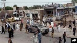Petugas keamanan Pakistan dan para wartawan mengerumuni lokasi ledakan bom mobil di Peshawar, Pakistan, Minggu pagi (30/6).
