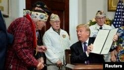 El presidente Donald Trump muestra a uno de los veteranos de Pearl Harbor, Lawrence Parry, la proclamación firmada y dijo que entregaría a los veteranos lapiceros para recordar el momento.