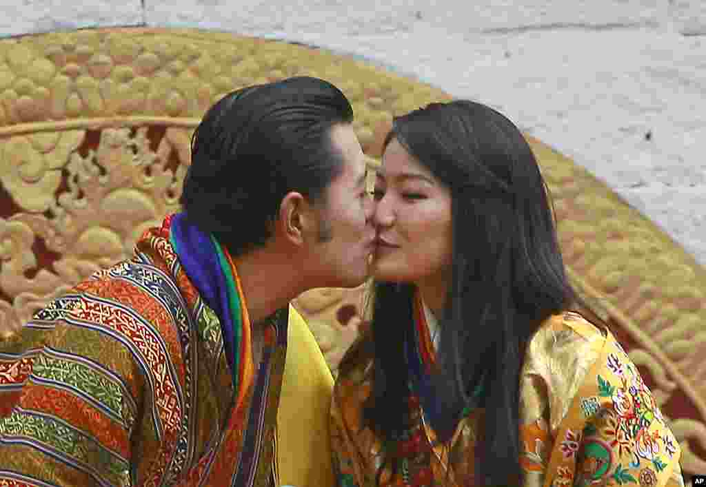 Bhutan's King Jigme Khesar Namgyel Wangchuck and Queen Jetsun Pema kiss in front of the crowd at the main stadium as part of their wedding celebrations in Thimphu, October 15, 2011. (AP)