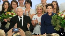 Conservative Law and Justice (PiS) leader Jaroslaw Kaczynski, left, and PiS candidate for prime minister Beata Szydlo, right, react to preliminary election results at the party's headquarters in Warsaw, Poland, Oct. 25, 2015.