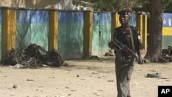 一名警官星期二在尼日利亞北部城市卡諾的一個被炸的警察局外走過。
