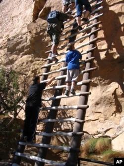 Visitors climb steep ladders on a tour of Balcony House, an ancient cliff dwelling in Mesa Verde National Park