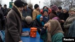 Warga Ukraina antri makanan yang dibagikan oleh separatis pro-Rusia di desa Chornukhyne, dekat Debaltseve, Ukraina timur (12/3). Konflik di Ukraina timur dilaporkan terus mereda.