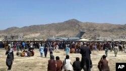 Njerëzit e mbledhur përreth një aeroplani transportues në aeroportin e Kabulit