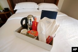 Items in a welcoming kit containing creature comforts that many Chinese travelers expect in their rooms, including, from the left, an electric kettle, green tea, instant noodles, slippers, and a robe, rest in a tray on a bed in Boston.