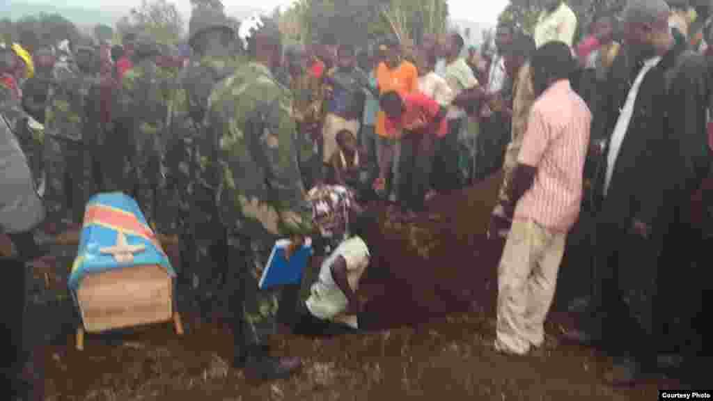 Un homme essaie de creuser un trou pour mettre le cercueil d'une victime, en RDC, Kamanyola dans le Sud-Kivu, 16 septembre 2017.
