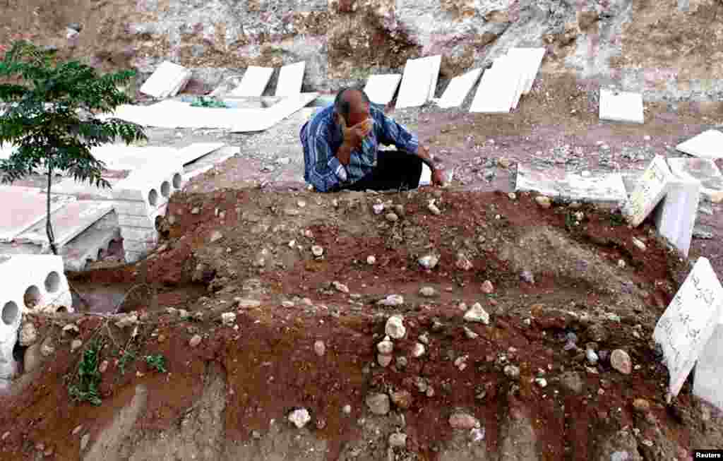 A man cries near the graves of his two children killed during a recent Syrian Air Force air strike in Azaz, August 20, 2012.
