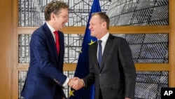 European Council President Donald Tusk, right, shakes hands with the chair of the Eurogroup Jeroen Dijsselbloem ahead of a meeting of eurozone finance ministers at the Europa building in Brussels on Dec. 4, 2017.
