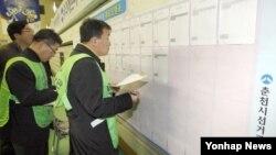 18대 대통령 선거를 마친 19일 개표집계상황표를 살펴보고 있는 강원 춘천시 개표소의 개표참관인들.