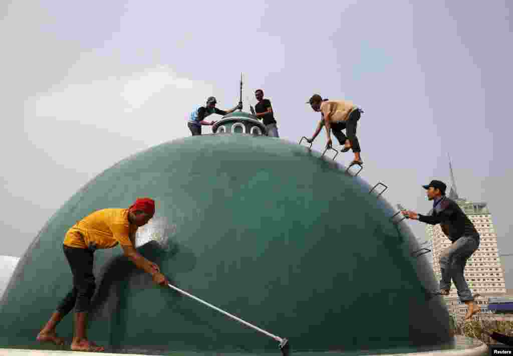 Youths clean the dome of a mosque ahead of the upcoming Muslim holy fasting month of Ramadan in Jakarta. Ramadan in Indonesia will start on June 18, a local paper reported.