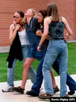 In this Tuesday, April 20, 1999 file photo, four unidentified young women head to a library near Columbine High School where students and faculty members were evacuated after two student gunmen went on a shooting rampage in the school near Denver.