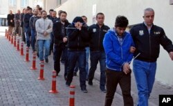 FILE - Police officers escort people arrested because of suspected links to U.S.-based cleric Fethullah Gulen — blamed by Ankara for the failed coup — in Kayseri, Turkey, April 26, 2017.