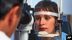 A young woman has her eyes examined by an ophthalmologist.