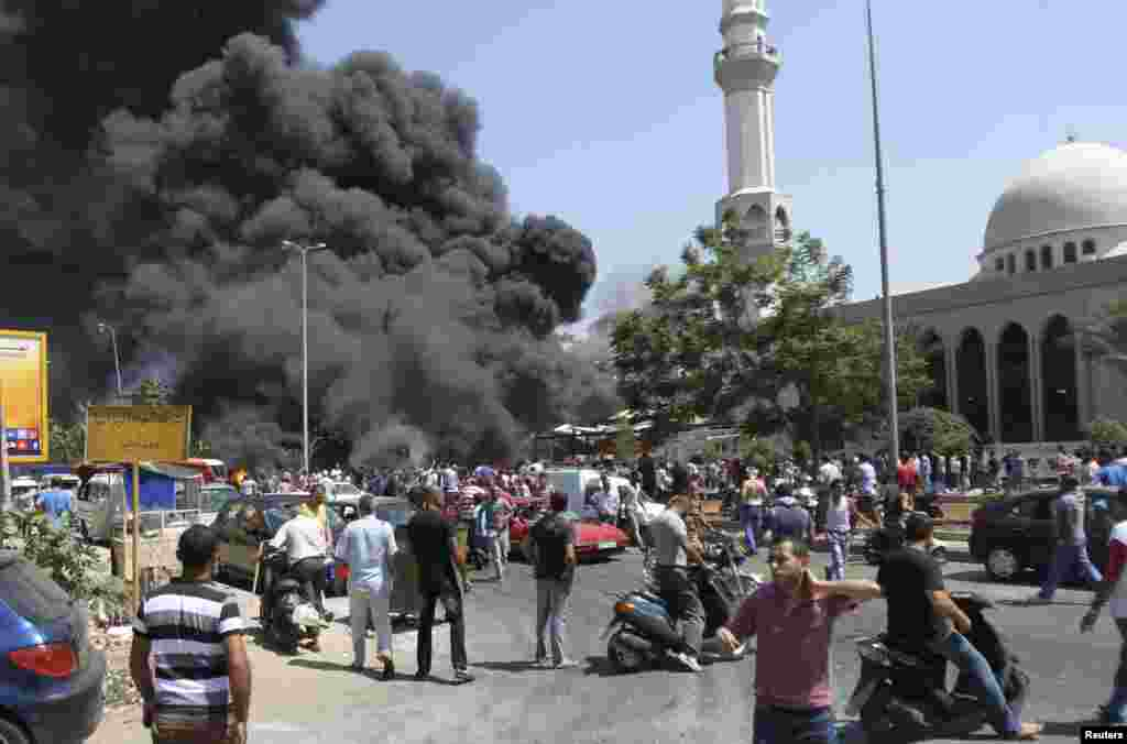 Smoke rises outside al-Taqwa mosque, one of two mosques hit by explosions, Tripoli, Lebanon, August 23, 2013.