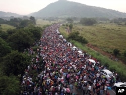 FILE - Members of a US-bound migrant caravan stand on a road after federal police briefly blocked their way outside the town of Arriaga, Saturday, Oct. 27, 2018.