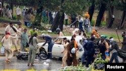 Para demonstran menggunakan tongkat untuk menghantam mobil dan motor dalam protes di Islamabad (1/9). (Reuters/Faisal Mahmood)