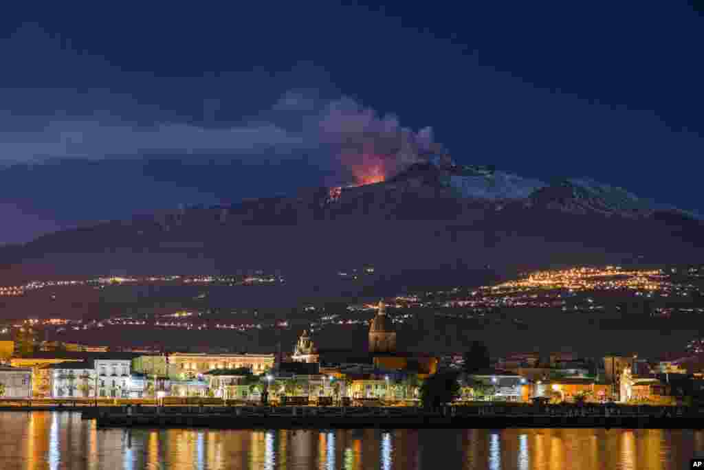 Mount Etna, Europe's most active volcano, spews lava during an eruption, with the Sicilian town of Riposto, Italy, visible in the foreground.