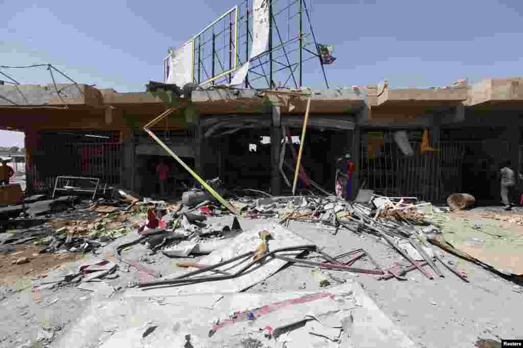 People inspect the site of a car bomb attack in the Ur district, northeastern Baghdad, Sept. 30, 2013.