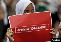 """Seorang siswi membawa poster bertuliskan """"pelajar tidak takut"""" dalam pawai memprotes aksi terorisme, sehari setelah serangan teror dan penembakan di Jakarta, 15 Januari 2016."""