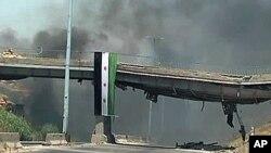 11일 시리아 정부군의 폭격 후 화염이 치솟는 홈스 시.