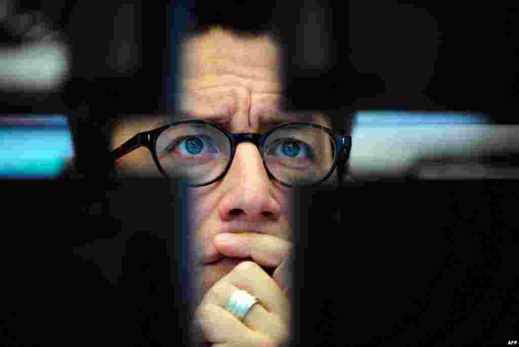 August 10: A broker looks at computer screens at the stock exchange in Frankfurt, Germany, where the stock index DAX went down again. (AP Photo/Patrick Sinkel)