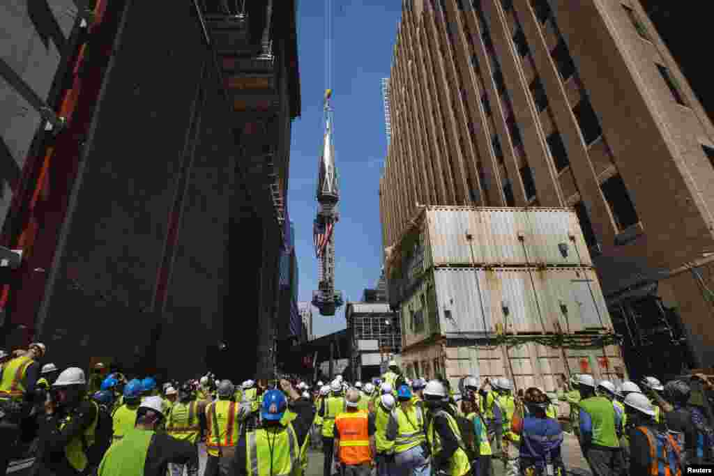 """Radnici, kamermani i fotoreportetri """"ispraćaju"""" u vis posljednji dio koji će se naći na vrhu Tornja 1 novog Svjetskog trgovinskog centra, podignutog na Ground Zero, prostoru na kojem su se nalazili oblakoderi starog Svjetskog trgovinskog centra, srušeni otetim avionima 11. septembra 2001. godine u najgorem i najtežem terorističkom napadu na SAD."""