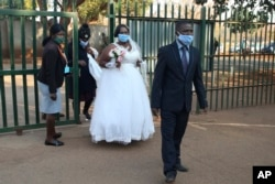 A bride and groom arrives to get married at the magistrates court, in Harare, Wednesday, Aug. 12, 2020. (AP Photo/Tsvangirayi Mukwazhi)