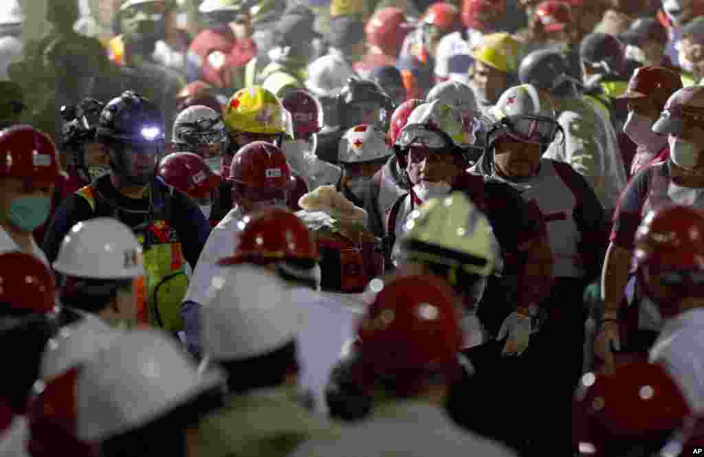 Rescue workers carry an injured survivor after an explosion in a building at Mexico's state-owned oil company PEMEX complex, in Mexico City, January 31, 2013.