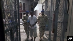 Detainee is escorted by guards inside Camp 6, a high-security detention facility at Guantanamo Bay U.S. Naval Base, Cuba., 30 Mar 2010 (file photo).