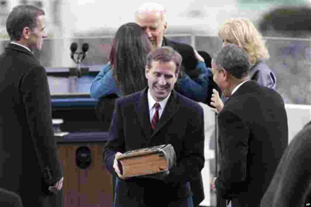 Beau Biden berbicara dengan Presiden Barack Obama di Taman Barat gedung DPR di Washington setelah ayahnya, Wakil Presiden Joe Biden (di belakang) diambil sumpahnya dalam Pelantikan Presiden ke-57, 21 Januari 2013.