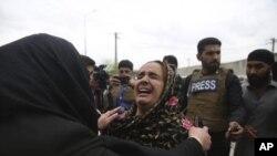 Familiares lloran desconsolados luego que un militante del grupo terrorista Estado Islámico irrumpiera armado con un fusil y granadas de mano y diera muerte a 25 personas en un templo sij en Kabul.