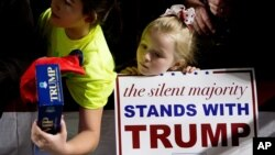 A young girl stands at the rope line at a rally in support of Republican presidential candidate Donald Trump at Muscatine High School in Muscatine, Iowa, Jan. 24, 2016.