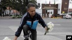Un hombre coloca flores en un memorial improvisado frente a la Academia de Policía General Francisco de Paula Santander, un día después de que explotara un coche bomba en el lugar.