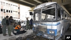 Two Syrian security men, left, look to a civil defense worker as he checks a dead body, next to a damaged riot police forces bus at the scene of a suicide bomb attack, at Midan neighborhood, in Damascus, Syria, on Friday Jan. 6, 2012.