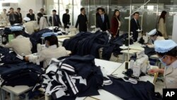 지난해 10월 한국 국회의원들이 개성공단을 현지 시찰하는 가운데, 개성공단 북한 노동자들이 작업에 열중하고 있다.