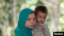 在泰国-马来西亚边界被拘留的一个疑似来自新疆的维吾尔人抱着一个孩子在临时收容所里(2014年3月14日)