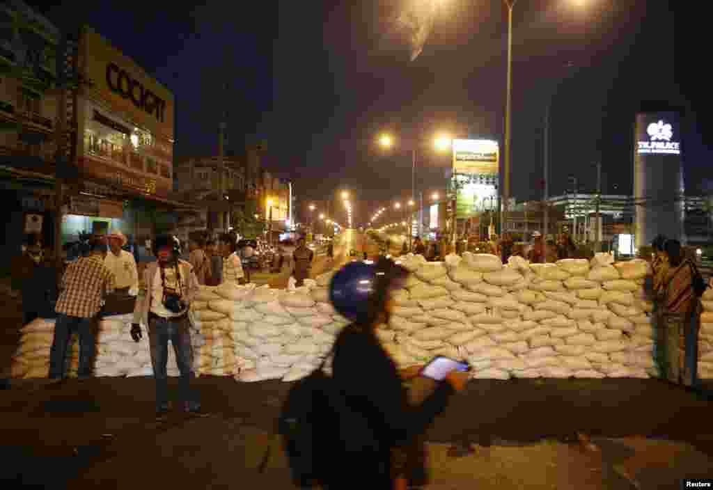 Người biểu tình chống chính phủ chờ phía sau hàng rào chướng ngại sau khi chặn con đường gần khu vực Tòa nhà Chính phủ ở Bangkok 12/1/14.