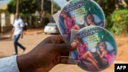 "FILE - A vendor displays CDs featuring Ugandan pop singer Jemimah Kansiime, also known as ""Panadol wa bassajja"" - literally, ""medicine for men"" - in Kampala, Uganda, April 17, 2015. The singer was indicted under an anti-pornography law."