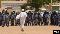 Anti-government protestor faces riot police last week in Khartoum (A. Ahmed/VOA).