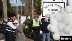 2013年12月15日,槍擊慘案發生一天后,人們在康涅狄克州紐頓市桑迪•胡克小學外沉痛哀悼死難師生。