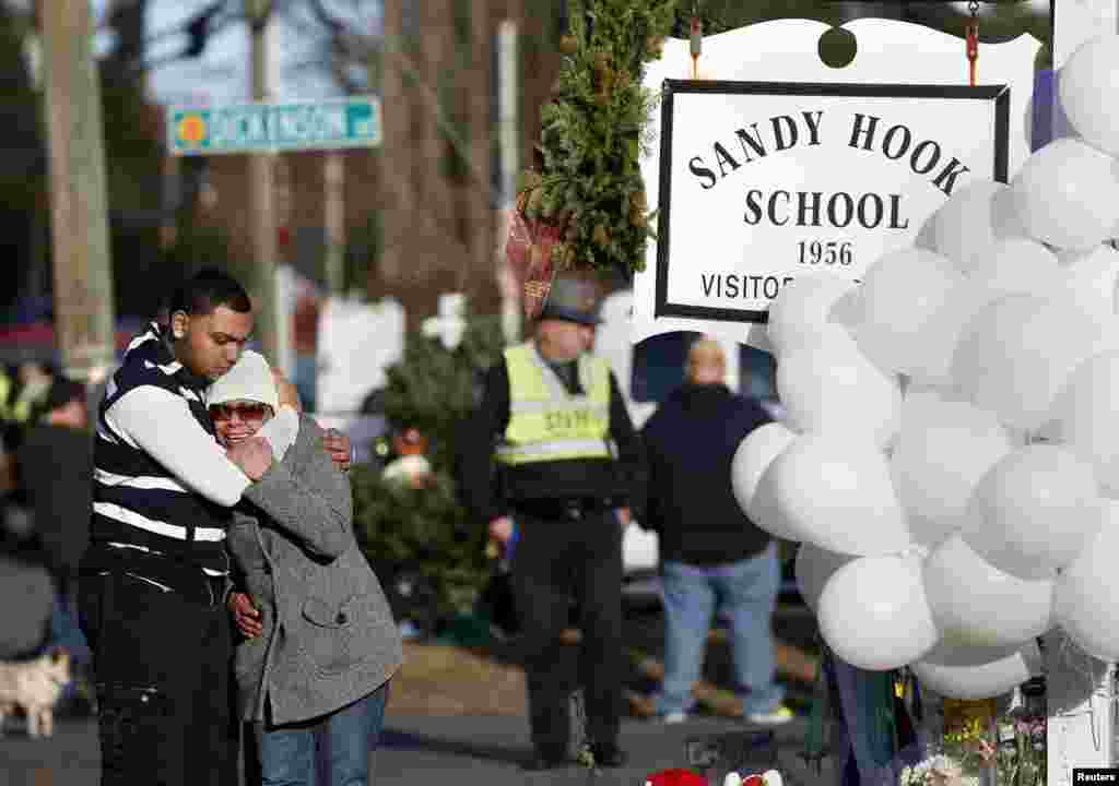People grieve next to a makeshift memorial of flowers and balloons next to the Sandy Hook Elementary school sign in Sandy Hook, Connecticut, Dec. 15, 2012.