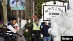 2012年12月15日,枪击惨案发生一天后,人们在康涅狄克州纽顿市桑迪•胡克小学外沉痛哀悼死难师生。