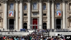 The tapestries showing the late Pope John Paul II and Pope John XXIII hang from the facade of St. Peter's Basilica as faithful and pilgrims crowd St. Peter's Square, April 25, 2014.